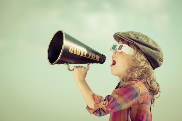 Ребенок кричит через старинный мегафон. концепция коммуникации. ретро стиль