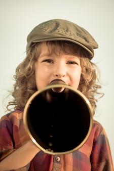 ヴィンテージメガホンを通して叫ぶ子供。コミュニケーションの概念。レトロなスタイル