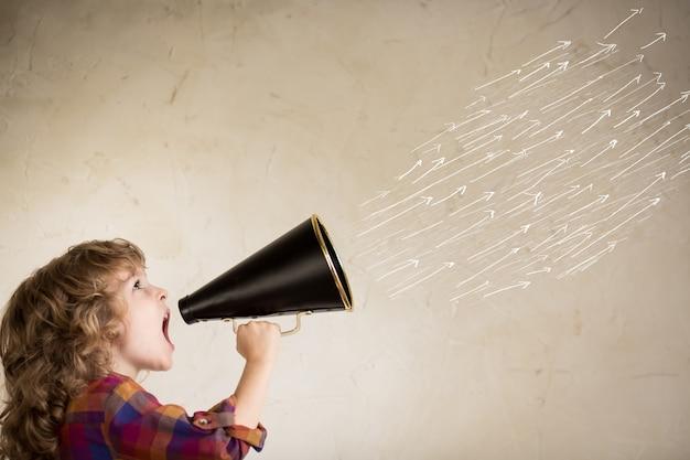 ヴィンテージメガホンを通して叫ぶ子供。コミュニケーションの概念。