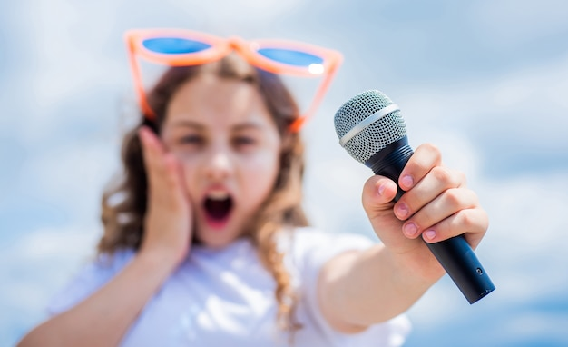 Kid sing with mic. selective focus. cheerful event manager. child have fun on party. happy singer with microphone. classic cool. girl singing. vocal school concept. karaoke club. music is my life.