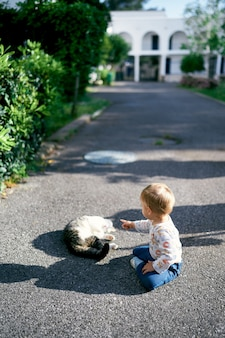 Kid sits on an asphalt path in the garden and points a finger at a sleeping cat