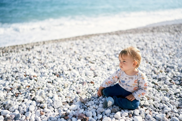 子供は海沿いの小石のビーチに座って遠くを見ます