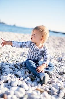 子供は海沿いの小石のビーチに座って、遠くに指を向けます