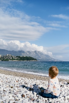 Kid sits on a pebble beach by the sea and looks at the island back view
