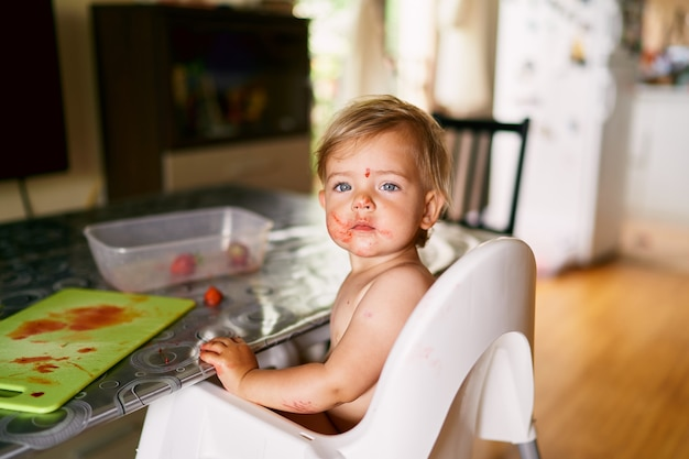 Kid sits at a table with a strawberrystained face