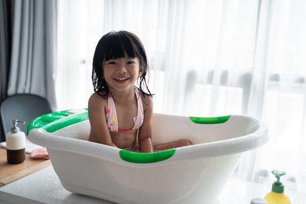 Kid sitting on a basin taking a bath