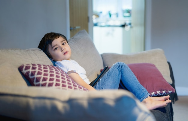 Kid sitting on sofa looking at camera with smiling face.