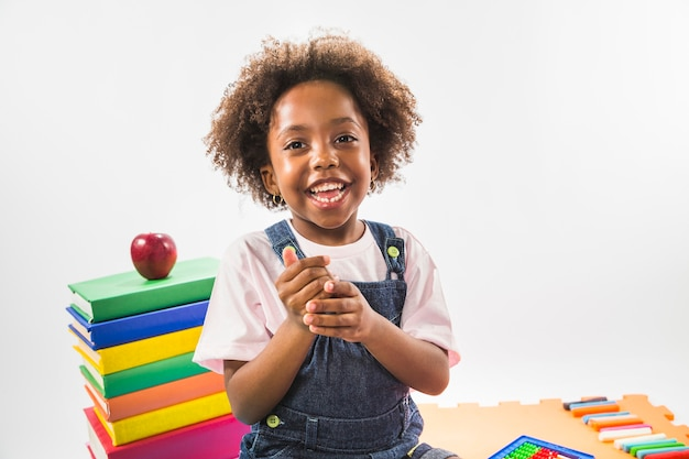 Kid sitting with books and smiling in studio