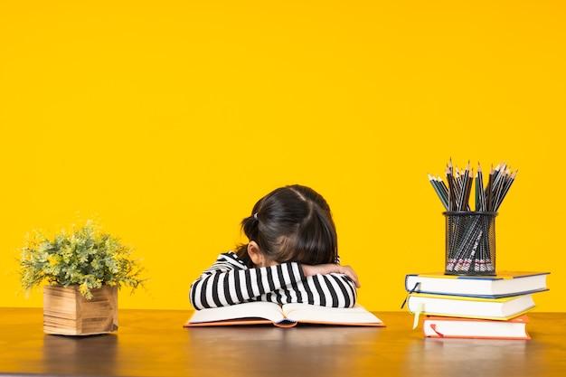 Ребенок спит на столе со стопкой книг