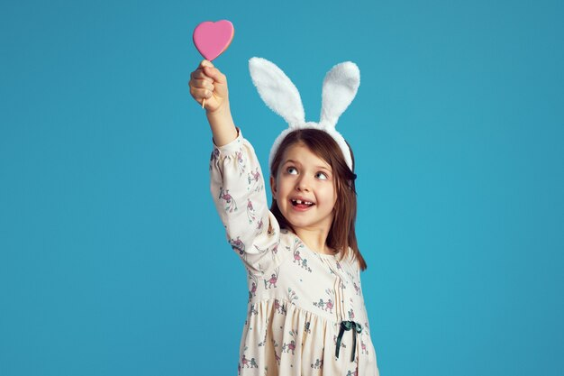 Ребенок улыбается и держит вкусное сладкое печенье в форме сердца в кроличьих ушах