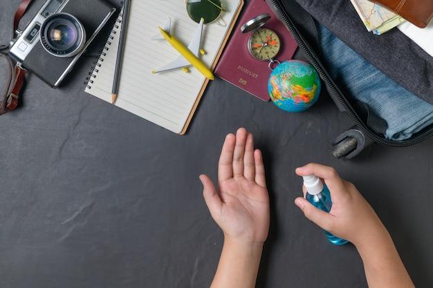 Детские брызги спирта под рукой и чемодан, старинный фотоаппарат, блокнот, карта на черном кафельном полу и место для копий. путешествия и предотвращение covid 19 концепции