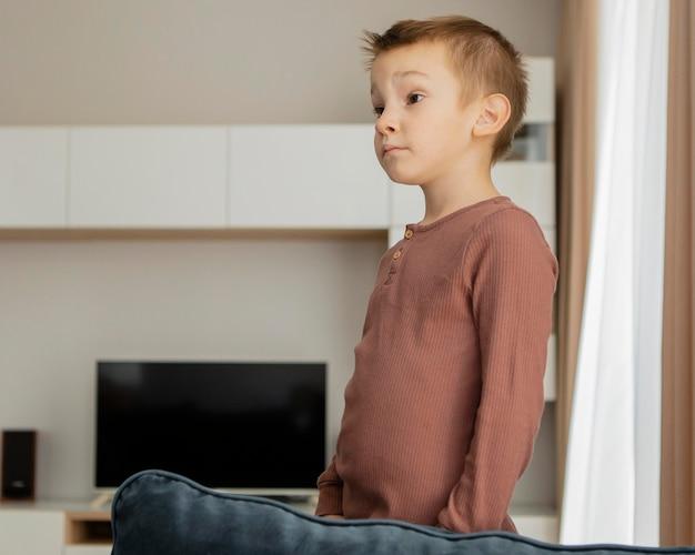Ребенок стоит на диване и смотрит в сторону