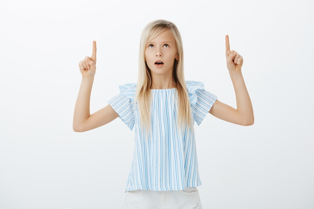 Kid standing still amazed with beehive. shocked and wondered adorable female child in blue blouse, raising hands, pointing and looking up with interested and curious expression over gray wall