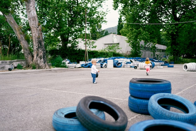 Kid stands on the playground against the background of many painted car tires