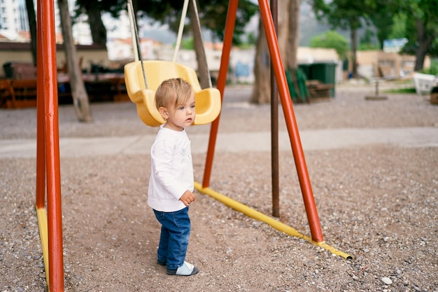 Kid stands on the playground holding the swing with his hand