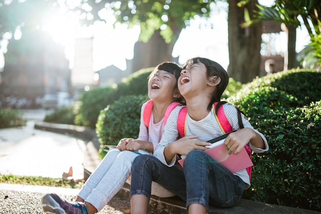 Kid students laughing while sitting in the park