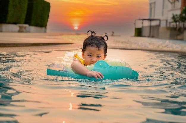 여름 방학에 수영장에서 수영하는 아이. 아시아 어린 소녀의 생활 방식과 휴식.