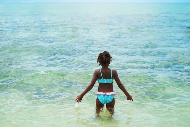 Ребенок плавает в кристально чистой воде, развлекаясь на прекрасном пляже