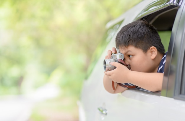 Kid take picture with vintage camera from window car