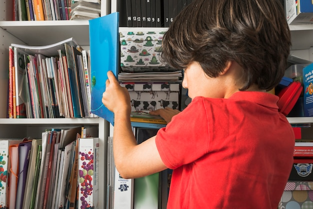 Kid taking book from shelf