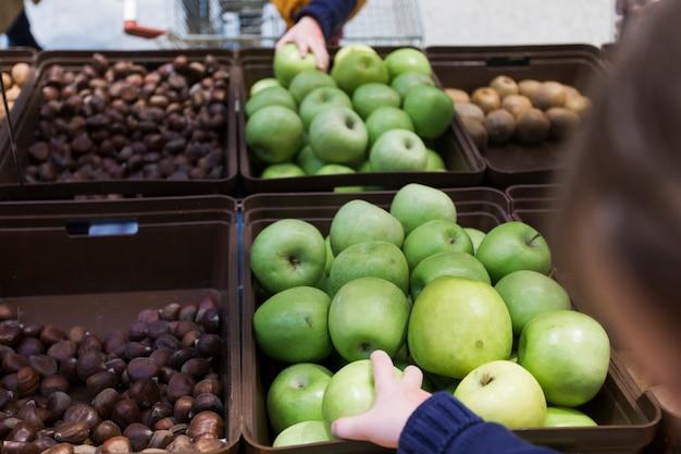 Kid taking green apple from shelf