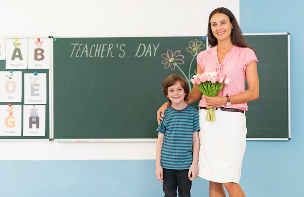 Kid and teacher holding a bouquet of flowers with copy space