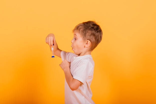 Kid time concept - serious male preschooler enjoying learning about time, holding an hour glass, studio shot
