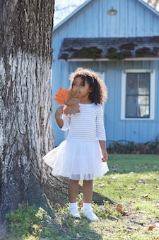 Kid toddler girl with autumn leaf playing outdoor