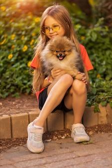 屋外で犬と遊ぶ子供の訓練小さな女の子は彼女の腕の中でスピッツを取りますペットを抱き締める子供幸せな赤ちゃんはポメラニアンの高品質の写真で歩いています