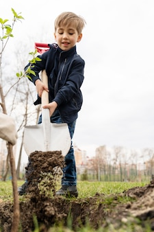야외에서 나무를 심 으려고하는 아이