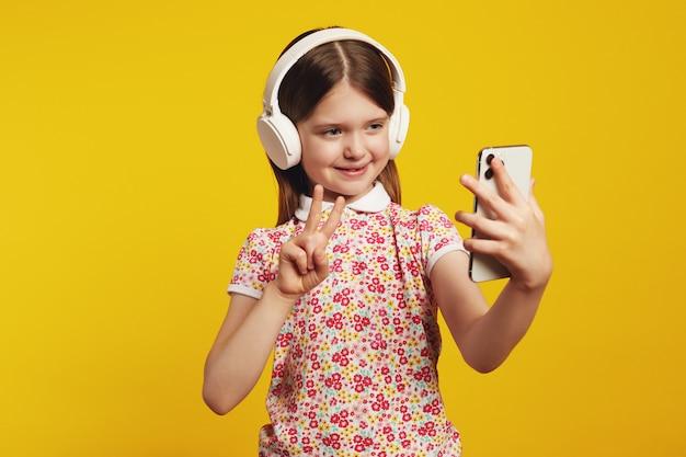 Ребенок использует смартфон, слушает музыку в белых наушниках, показывает жест мира