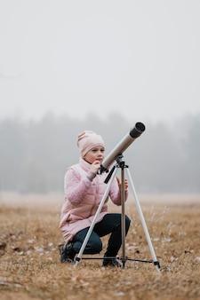 밖에서 망원경을 사용하는 아이