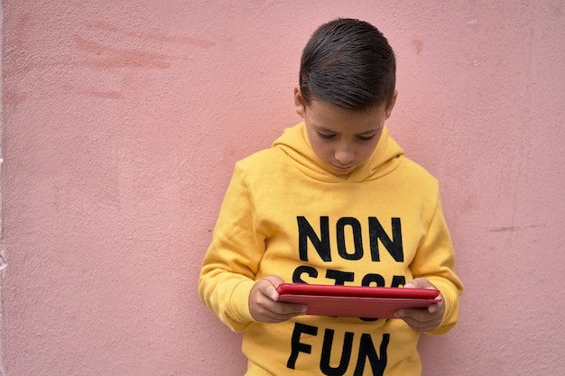 Kid using his digital tablet on the street