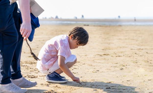 子供が海で歩いているぼやけた人々と暑い晴れた日に砂に書いて彼の指を使用して、家族の休日、祖母の足のぼやけた前景と海のビーチで遊んでいる子供男の子