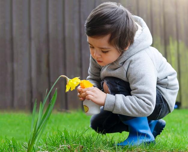 Kid using spray bottle watering flowers in the garden