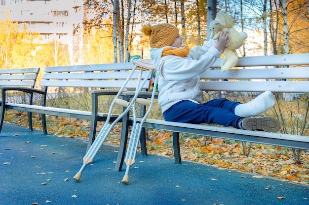 Kid walks in autumn park on crutches child sitting