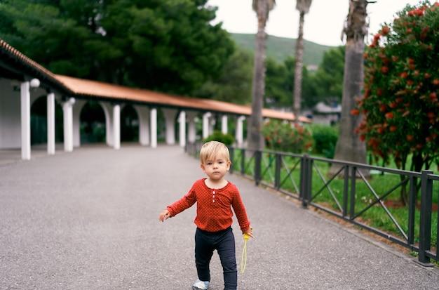 緑に囲まれた公園の長いパビリオンを背景にアスファルトの上を歩く子供