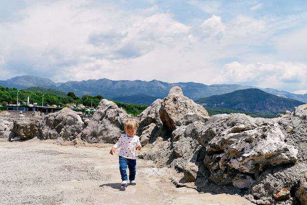 Kid walks on a stone platform with boulders against a background of mountains