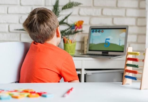 Kid watching video on laptop