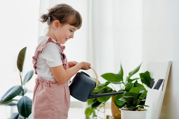 自宅で植物に水をまく子供の