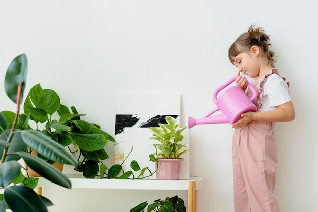 Bambino che innaffia le piante a casa