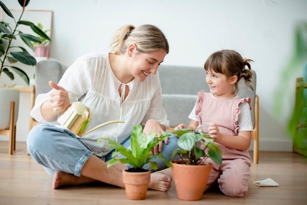 家で鉢植えの植物に水をまく子供