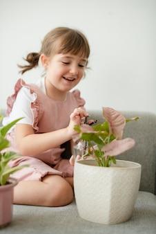 Bambino che innaffia le piante in vaso a casa