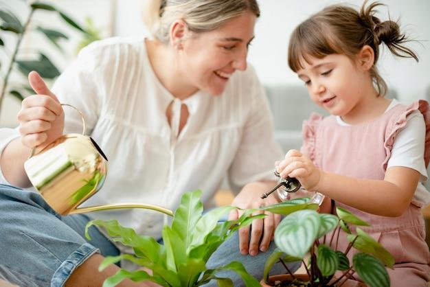 家でお母さんと鉢植えの植物に水をまく子供