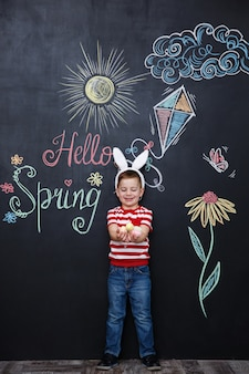 Kid wearing bunny ears and holding heap of easter eggs