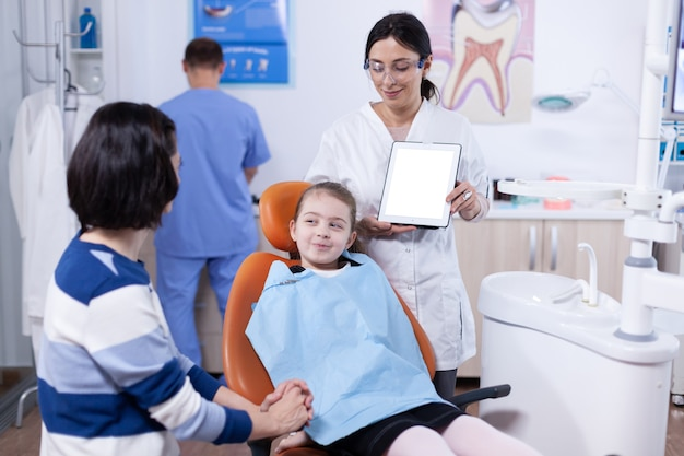 치과 턱받이를 착용하고 의사가 충치 치료에 대해 부모와 논의하는 아이. stomatolog는 복사 공간이 있는 태블릿 pc를 들고 있는 엄마와 아이에게 치아 예방을 설명합니다.