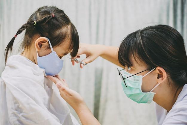 理髪店で髪をカットしながらコロナウイルスを防ぐためにフェイスマスクを着ている子供