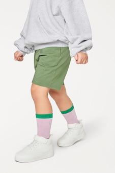 灰色のスウェットシャツの白いスニーカーを着ている子供
