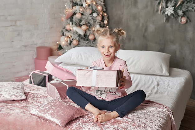 Kid wearing pajamas and opening christmas present