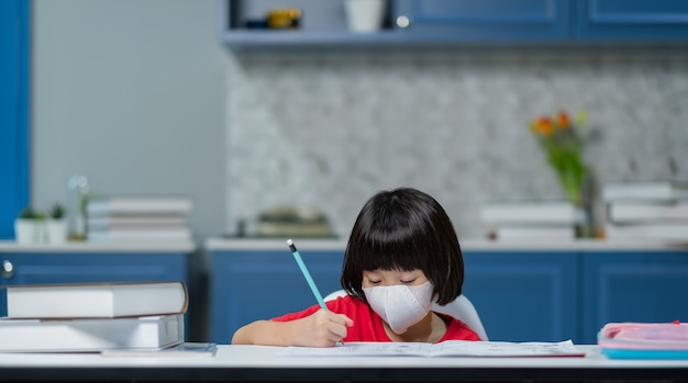Kid wearing protect mask and doing homework, child writing paper, education concept
